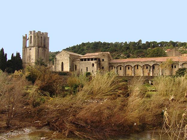 Fig. 1 - Front oriental de l'abbaye, vu depuis l'Orbieu : clocher (à gauche), chevet de l'église, tour préromane et dortoir (à droite)